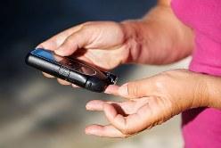 指先に測定器をつけて血糖値を測る様子