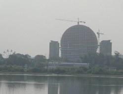 中朝国境を流れる鴨緑江北朝鮮側に建設中の太陽を模した建物。ホテルと見られていたが、北朝鮮紙はアパートだと伝えている=2019年8月撮影