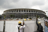 In this July 24, 2019, file photo, workers adjust fences at the construction site of the New National Stadium, a venue for the opening and closing ceremonies at the Tokyo 2020 Olympics, in Tokyo. (AP Photo/Jae C. Hong)