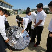太陽傘で温められた缶内部の水温を計る印南中の生徒たち=印南町印南の同校内で、山本芳博撮影