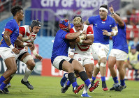Japan's Lomano Lava Lemeki runs at the Samoan defense during the Rugby World Cup Pool A game at City of Toyota Stadium between Japan and Samoa in Tokyo City, Japan, Saturday, Oct. 5, 2019. (AP Photo/Shuji Kajiyama)