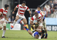 Japan's James Moore, right, is tackled by a Samoan defender during the Rugby World Cup Pool A game at City of Toyota Stadium between Japan and Samoa in Tokyo City, Japan, Saturday, Oct. 5, 2019. (AP Photo/Shuji Kajiyama)