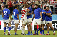 Japan's Michael Leitch embraces Samoan players after their Rugby World Cup Pool A game at City of Toyota Stadium in Tokyo City, Japan, Saturday, Oct. 5, 2019. Japan defeated Samoa 38-19.(AP Photo/Shuji Kajiyama)