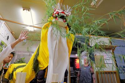 大槌稲荷神社例大祭の宵宮の後、仮設商店街の「大槌北小 七福食堂」を訪れた虎舞を見つめる店主の小川勝子さん(右奧)。「過ぎてみると早いが、長い8年だった。新しい店に移って初めて私たちの復興は始まります」。今年の年末には大槌駅前の商業施設に移ることが決まっている=岩手県大槌町で2019年9月20日、和田大典撮影