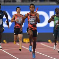 男子400メートルリレー予選2組、第3走者の桐生祥秀(中央奥)からバトンを受けて走り出すアンカーのサニブラウン・ハキーム(同手前)=カタール・ドーハで2019年10月4日、久保玲撮影