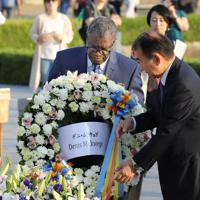 原爆慰霊碑に献花するデニ・ムクウェゲ氏(左)=広島市中区の原爆資料館で、大西達也撮影