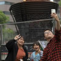 炬火台をバックに写真と撮る人たち=埼玉県川口市で2019年10月6日午前11時9分、玉城達郎撮影