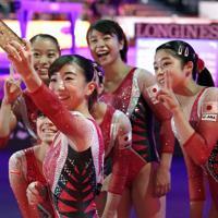 女子予選を終えて記念撮影する寺本明日香(手前)ら女子日本代表の選手たち=ドイツ・シュツットガルトで2019年10月5日、宮間俊樹撮影
