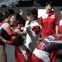 女子予選の床運動の演技を終えた松村朱里(左端)と抱き合う寺本明日香ら日本代表の選手たち=ドイツ・シュツットガルトで2019年10月5日、宮間俊樹撮影