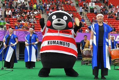 【フランス-トンガ】日本代表の桜のジャージーを着てパフォーマンスするくまモン(中央)=えがお健康スタジアムで2019年10月6日、徳野仁子撮影