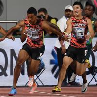 男子400メートルリレー決勝、第3走者の桐生祥秀(手前右)からバトンを受けて走り出すアンカーのサニブラウン・ハキーム=カタール・ドーハで2019年10月5日、久保玲撮影