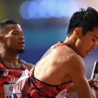 男子1600メートルリレー予選1組、第1走者のウォルシュ・ジュリアン(左)からバトンを受け取る第2走者の飯塚翔太=カタール・ドーハで2019年10月5日、久保玲撮影