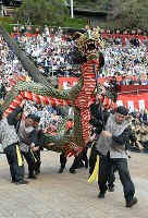 People dressed in Chinese costumes maneuver a 20-meter-long dragon as part of a performance called