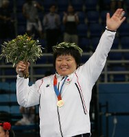 2004 Athens Olympics -- Japan's Maki Tsukada is awarded the gold medal in the over-78-kilogram division of women's judo. She defeated Cuba's Daima Beltran in the final by ippon with a holding technique after giving a waza-ari point to her opponent. (Mainichi/Takeshi Noda)