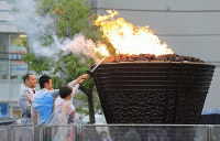 From left, Olympic medalist Koji Murofushi, local high school student Takuma Urabe and junior high student Rinka Hayashi are seen lighting the Olympic cauldron used in the 1964 Tokyo Olympics, in Kawaguchi, Saitama Prefecture, on Oct. 6, 2019. (Mainichi/Tatsuro Tamaki)