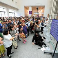 再開された「表現の不自由展・その後」観覧の抽選で、当選番号を発表するテレビ画面に見入る人たち=名古屋市東区の愛知芸術文化センターで2019年10月8日午後1時39分(代表撮影)