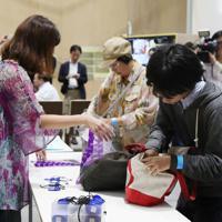 再開された「表現の不自由展・その後」への入場を前に手荷物を預ける来場者(右)=名古屋市東区の愛知芸術文化センターで2019年10月8日午後1時50分(代表撮影)