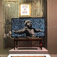 ゴミの焼却灰を雪だと思って喜ぶ少年の絵は大型テレビに映し出されている=ロンドン南部で6日、横山三加子撮影