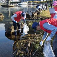 水辺でごみ拾いする参加者=長野県諏訪市湖岸通りの石彫公園で