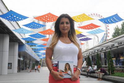 自らの半生をつづった著書を手に、東京五輪への期待を語るサリマ・スアクリさん=東京都内で2019年8月26日午後1時9分、田原和宏撮影