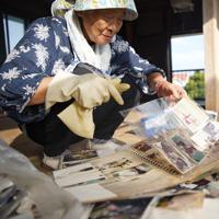 雨に濡れた写真アルバムを整理する安西えみさん(79)。「日なたで乾かしているけど、半分はだめそう。思い出がなくなるようで寂しいね」とつぶやいた=千葉県鋸南町で2019年10月8日午後2時52分、玉城達郎撮影