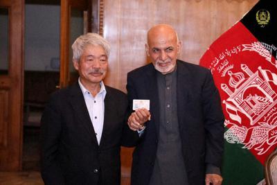 ガニ大統領(右)から市民証を受けた中村哲医師=アフガニスタン大統領官邸提供