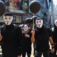 お面を顔につけてデモに参加する市民ら=香港・銅鑼湾で2019年10月1日、福岡静哉撮影