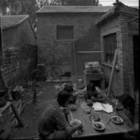 画筆を箸にして食事をする画家たち=円明園画家村で1992年、徐志偉氏提供