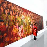 第11回宋荘文化芸術祭に出品された油絵の前でポーズを撮る親子=北京・宋荘画家村で、浦松丈二撮影