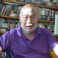 「社会に溶け込めないやつが来ればいいんだ」と話す伊靈氏=北京・宋荘画家村で、浦松丈二撮影