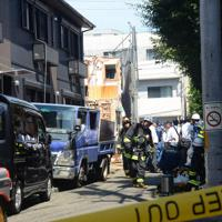 2人が死亡したアパート(左)。遺体発見から2時間がたっても、室内はCO濃度が高く、捜査員らは室内に入れなかった=東京都世田谷区で、土江洋範撮影