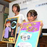 田川署で受賞作を手にする原さん(左)と荒川さん