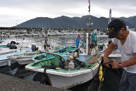 Fishermen are seen tightly mooring boats in preparation for upcoming powerful Typhoon Hagibis, in the central Japan city of Owase, Mie Prefecture, on Oct. 10, 2019. (Mainichi/Emi Shimomura)
