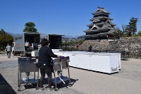 Workers are seen packing away cooking counters for a soba noodles festival after it was canceled due to oncoming powerful Typhoon Hagibis, at the Matsumoto Castle Park in the central Japan city of Matsumoto, Nagano Prefecture, on Oct. 10, 2019. (Mainichi)