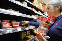 A woman grabs many packets of cup ramen noodles in preparation for powerful Typhoon Hagibis at a supermarket in Tokyo's Taito Ward on Oct. 11, 2019. (Mainichi/Yuki Miyatake)