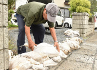 A man piles up sandbags in front of his house in preparation for powerful Typhoon Hagibis, in the eastern Japan city of Mito on Oct. 11, 2019. (Mainichi/Kyoka Kobayashi)