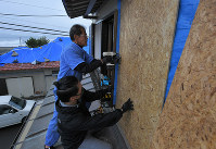 Men attach plywood boards to a wall that was broken by flying objects when Typhoon Faxai hit in September, in preparation for powerful Typhoon Hagibis in the Chiba Prefecture city of Tateyama, east of Tokyo, on Oct. 11, 2019. (Mainichi/Koichiro Tezuka)