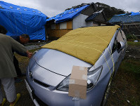 Residents cover a car to prevent it from being damaged by flying objects, in preparation for powerful Typhoon Hagibis in the Chiba Prefecture city of Tateyama, east of Tokyo, on Oct. 11, 2019. Pictured at rear are houses which were damaged by Typhoon Faxai in September. (Mainichi/Koichiro Tezuka)