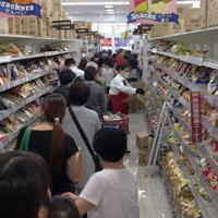 台風19号に備えてスーパーに買い出しに来た人たち。レジ待ちの行列は数十㍍になり、飲料水とカセットコンロ用のボンベは開店後まもなく売り切れた=横浜市神奈川区で2019年10月11日午前9時50分、丸山博撮影