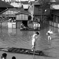 狩野川台風に襲われた日から4日、水が引かない東京都足立区高砂町の一帯。廃材に乗って水上を移動する住民=東京都足立区千住で、1958年9月30日