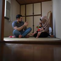 自宅で妻イマーンさん、長男アダムちゃんと一緒にスマートフォンでシリアに住む家族と話すバラさん(左)=川崎市で2019年8月10日、久保玲撮影