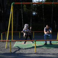 自宅近くの公園で妻イマーンさん、長男アダムちゃんと過ごすバラさん(右)=川崎市で2019年8月10日、久保玲撮影