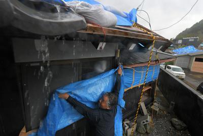 台風19号の接近に備え、風雨が強まる中、ガラス窓にビニールシートを張る庄司一則さん(62)。築100年になるこの家屋で古民家カフェを10月に開店させようと準備してきたが、台風15号で被災した。「屋根のシートは台風ではもたないと思うけど、瓦が飛んで周りの住宅に被害を与えるのを防いでくれれば」と作業を進めた=千葉県館山市布良で2019年10月11日午後0時48分、手塚耕一郎撮影