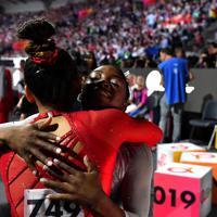 女子個人総合決勝で優勝を決めて米国のスニーサ・リー(手前)と抱き合う米国のシモーン・バイルス=ドイツ・シュツットガルトで2019年10月10日、宮間俊樹撮影