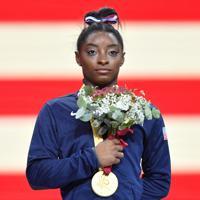 女子個人総合決勝で優勝し表彰式で金メダルを胸に国歌を聞く米国のシモーン・バイルス=ドイツ・シュツットガルトで2019年10月10日、宮間俊樹撮影