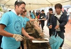 サンマの収穫祭で、焼きたてのサンマを受け取る来場者=宮城県女川町で2018年