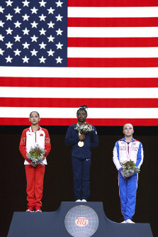 Gold medal winner Simone Biles of the U.S., center, second placed Xijing Tang of China, left, and third placed Angelina Melnikova of Russia celebrate on the podium after the women's all-around final at the Gymnastics World Championships in Stuttgart, Germany, on Oct. 10, 2019. (AP Photo/Matthias Schrader)