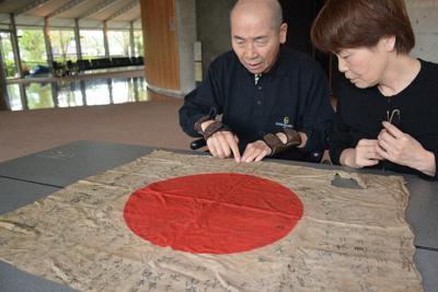 イギリスから届いた日章旗を食い入るように見つめる辰巳善昭さん(左)=奈良県大淀町で、萱原健一撮影