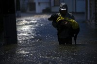 A man holding a dog evacuates while walking along a road in the city of Kawasaki flooded by rain from Typhoon Hagibis on the evening of Oct. 12, 2019. (Mainichi/Masahiro Ogawa)