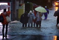 People evacuate along a road flooded due to Typhoon Hagibis in the city of Kawasaki on the evening of Oct. 12, 2019. (Mainichi/Masahiro Ogawa)